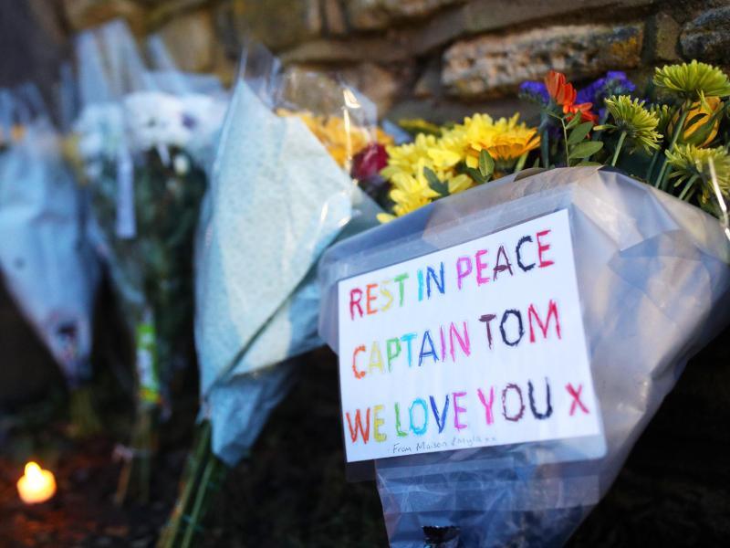 Blumen vor dem Haus von Tom Moore:'Rest in Peace, Captain Tom - We love you' (Ruhe in Frieden, Captain Tom - Wir lieben dich). Foto: Yui Mok/PA Wire/dpa