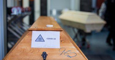 """Ein Sarg mit einem Verstorbenen mit der Aufschrift """"Covid 19"""" und dem Zeichen """"Biohazard"""" wird von einem Bestatter ein Krematorium eingeliefert. Foto: Rolf Vennenbernd/dpa"""