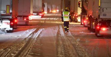 Ein THW-Mitarbieter betreut Lkw-Fahrer, die auf der Autobahn 4 bei Gera im Schnee stecken geblieben sind. Der Verkehr kam in Richtung Erfurt an einem Berg komplett zum erliegen. Foto: Bodo Schackow/dpa-zentralbild/dpa