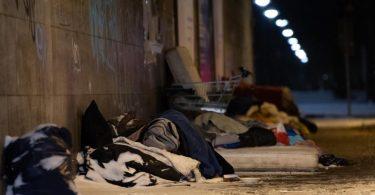 Obdachlose haben bei eisigen Temperaturen und Schnee unter einer Brücke am Bahnhof Zoo in Berlin ihr Lager errichtet und schlafen. Foto: Paul Zinken/dpa