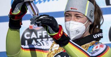 Kira Weidle hängt sich voller Freude die Silbermedaille bei der Siegerehrung selbst um den Hals. Foto: Jean-Christophe Bott/KEYSTONE/dpa