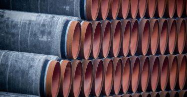 Rohre für die Erdgaspipeline Nord Stream 2 liegen auf einem Lagerplatz im Hafen Mukran auf der Insel Rügen. Foto: Jens Büttner/dpa-Zentralbild/dpa