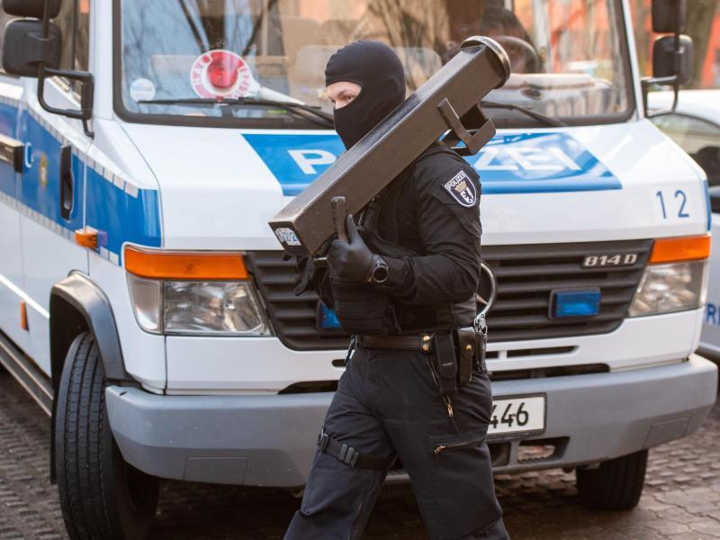 Ein Polizeibeamter trägt nach einer Razzia im Märkischen Viertel in Berlin eine Ramme. Foto: Christophe Gateau/dpa
