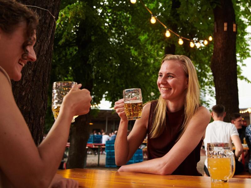 Zwei Frauen trinken ein Bier im Prater Biergarten in Berlin. Foto: Annette Riedl/dpa/Archiv