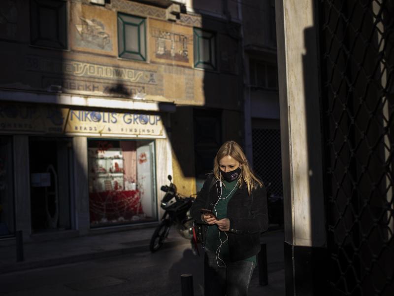 Eine Frau, die eine schützende Gesichtsmaske trägt, geht im Zentrum von Athen. Foto: Petros Giannakouris/AP/dpa