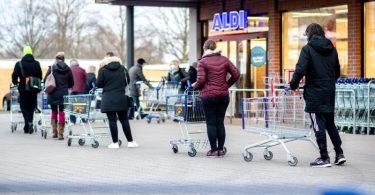 Zahlreiche Kunden warten auf die Öffnung einer Filiale von Aldi in Hannover. Der Discounter bietet nun Corona-Schnelltests zu Verkauf an. Foto: Hauke-Christian Dittrich/dpa