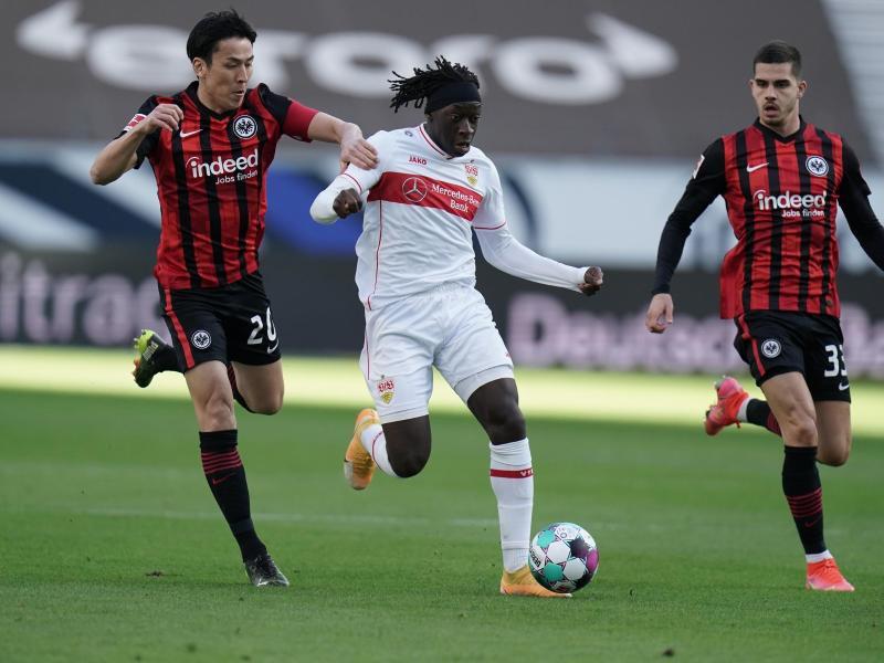 Stuttgarts Mittelfeldspieler Tanguy Coulibaly (M) versucht sich im Dribbling gegen zwei Frankfurter Gegenspieler durchzusetzen. Foto: Thomas Frey/dpa