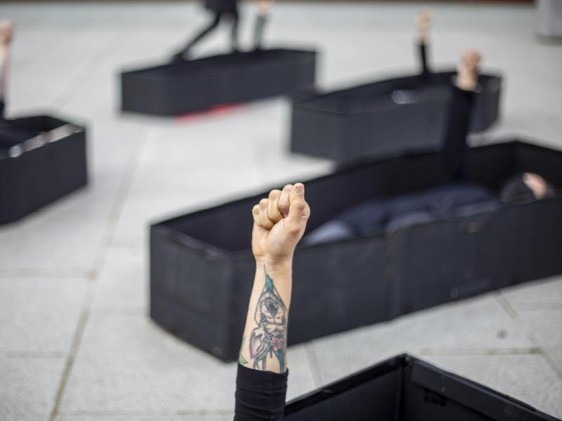 Frauen heben ihre Fäuste, während sie bei einer Demonstration im Vorfeld des Internationalen Frauentages vor dem Bundesgericht von Tel Aviv in Särgen liegen. Die Särge repräsentieren Frauen, die durch häusliche Gewalt getötet wurden. Foto: Ariel Schalit/AP/dpa