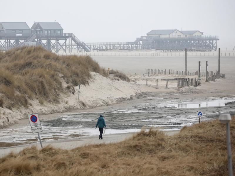 Eine Spaziergängerin ist bei regnerischem und windigem Wetter am Strand von St. Peter-Ording unterwegs. Nach Angaben des Deutschen Wetterdienstes werden an der Nordsee Böen mit Windgeschwindigkeiten bis zu 110 km/h erwartet. Foto: Bodo Marks/dpa