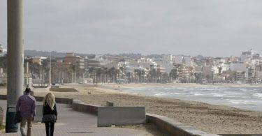 Spaziergänger auf der Promenade am Strand von Arenal. Foto: Clara Margais/dpa