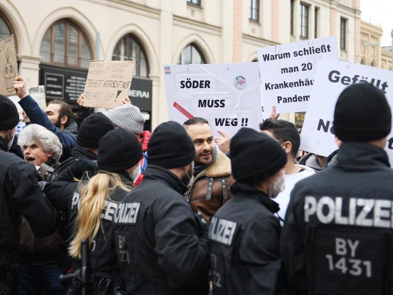 Polizisten hindern Teilnehmer der aufgelösten Demonstration in München daran weiterzuziehen. Foto: Angelika Warmuth/dpa