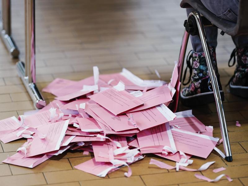 Geöffnete Wahlbriefumschläge liegen vor der Stimmauszählung in der Gartenhalle im Kongresszentrum in Karlsruhe neben einem Wahlhelfer auf dem Boden. Foto: Uwe Anspach/dpa