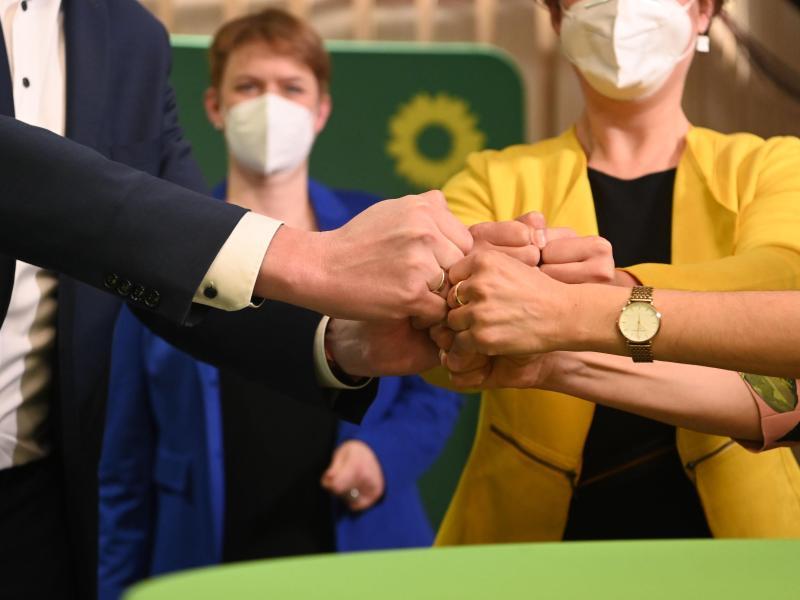 Mitglieder und Anhänger von Bündnis 90/Die Grünen bringen ihre Fäuste zusammen nach der Bekanntgabe der ersten Prognose zum Ergebnis der Landtagswahlen in Baden-Württemberg. Foto: Marijan Murat/dpa
