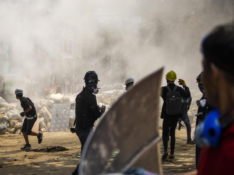 Demonstranten stehen vor rauchenden Trümmern einer provisorischen Barrikade bei einem Anti-Putsch-Protest in Yangon. Myanmarische Sicherheitskräfte haben heute erneut Waffengewalt gegen eine Demonstration gegen die Militärjunta eingesetzt. Foto: Uncredited/AP/dpa
