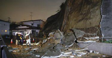 Menschen stehen vor eingestürzten Teilen einerKlippe. Eine Tsunami-Warnung in Folge eines starken Erdbebens im Nordosten Japans ist wieder aufgehoben worden. Foto: ---/Kyodo/dpa