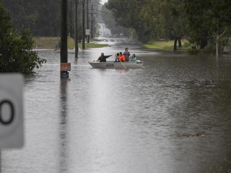 Menschen paddeln mit ihrem Boot durch das Wasser in einem Vorort von Sydney. Foto: Mark Baker/AP/dpa