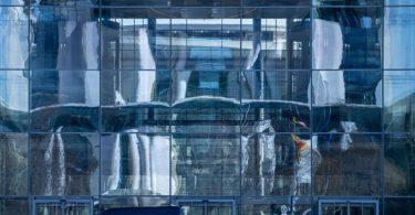 Die Fassade des Bundeskanzleramts spiegelt sich im Paul-Löbe-Haus des Bundestags. Im Kanzleramt berät Kanzlerin Merkel in einer Videokonferenz mit den Regierungschefs der Länder. Foto: Michael Kappeler/dpa
