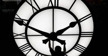 Ein Techniker bewegt die Uhrzeiger einer 500 kg schweren Uhr. Foto: Elise Amendola/AP/dpa