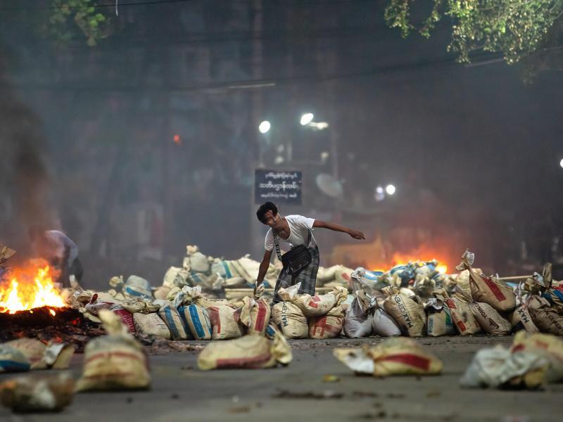 Ein Demonstrant stapelt Säcke auf einer Straße als Barrikade während eines Protestes in Yangon. Foto: Theint Mon Soe/SOPA Images via ZUMA Wire/dpa