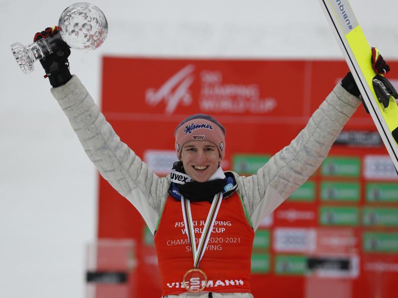 Karl Geiger feiert seinen Sieg auf dem Podium. Foto: Uncredited/AP/dpa