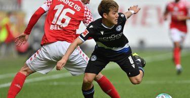 Mainz' Abwehrspieler Stefan Bell (l) versucht Bielefelds Stürmer Ritsu Doan vom Ball zu trennen. Foto: Torsten Silz/dpa