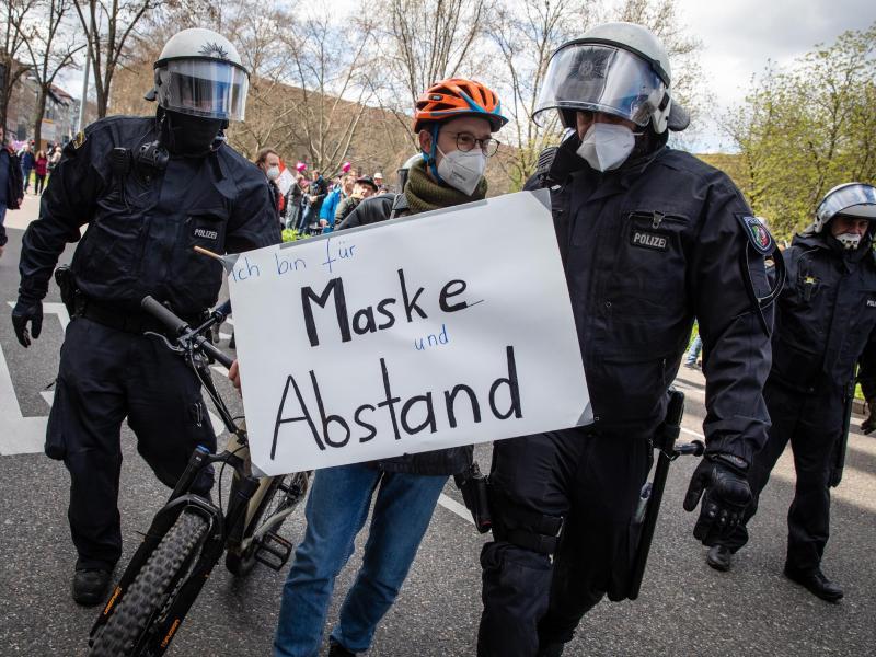 «Ich bin für Maske und Abstand» steht auf dem Schild eines Gegendemonstranten. Foto: Christoph Schmidt/dpa