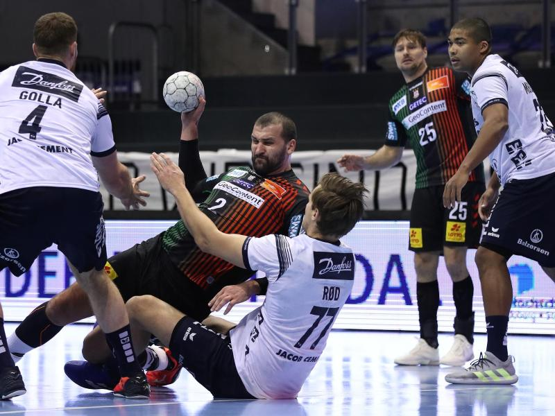 Die SG Flensburg-Handewitt (weiße Trikots) verteidigte in Magdeburg die Tabellenführung in der Handball-Bundesliga. Foto: Ronny Hartmann/dpa