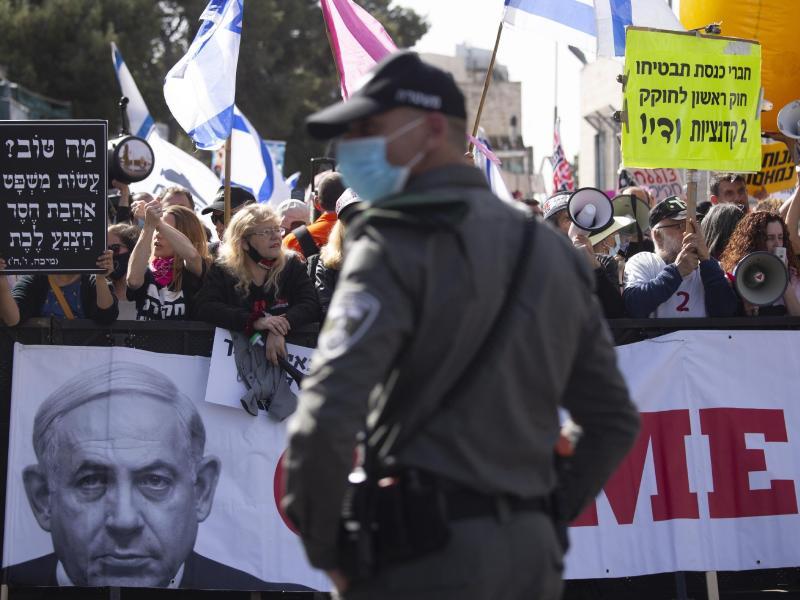 Demonstranten stehen mit Bannern und Plakaten vor dem Bezirksgericht in Jerusalem. Foto: Maya Alleruzzo/AP/dpa