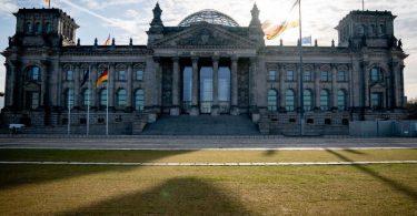 Die Sonne steht am Morgen hinter dem Reichstagsgebäude mit dem Bundestag. Foto: Kay Nietfeld/dpa