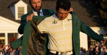 Hideki Matsuyama zieht sich mit Hilfe von Dustin Johnson das legendäre grüne Sieger-Jackett an. Foto: David J. Phillip/AP/dpa