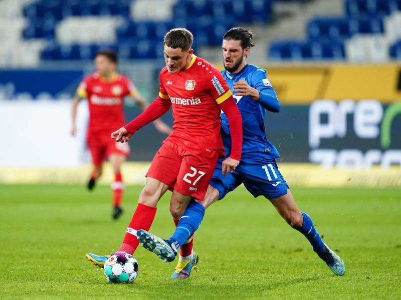 Leverkusens Florian Wirtz und Hoffenheims Florian Grillitsch (r) kämpfen um den Ball. Foto: Uwe Anspach/dpa