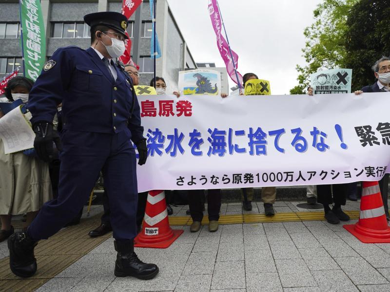 Menschen halten während einer Kundgebung vor dem Büro des Premierministers Suga ein Banner mit der Aufschrift «Werft kein radioaktives Wasser ins Meer». Foto: Eugene Hoshiko/AP/dpa