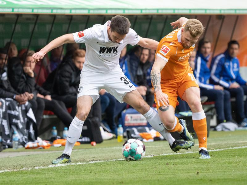 Augsburgs Raphael Framberger (l) und Bielefelds Andreas Voglsammer kämpfen an der Seitenauslinie um den Ball. Foto: Matthias Balk/dpa
