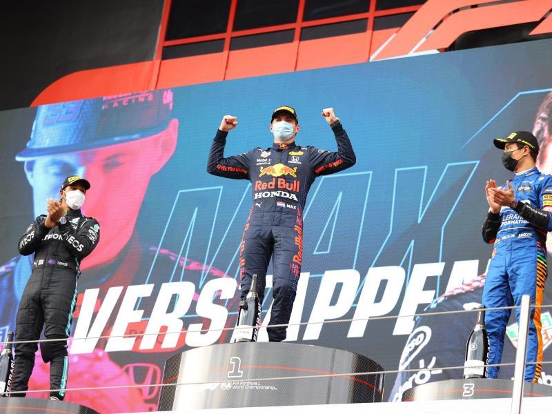 Sieger Max Verstappen (M) steht mit dem Zweitplatzierten Lewis Hamilton (l) und dem Drittplatzierten Lando Norris auf dem Podium. Foto: Bryn Lennon/AP/dpa