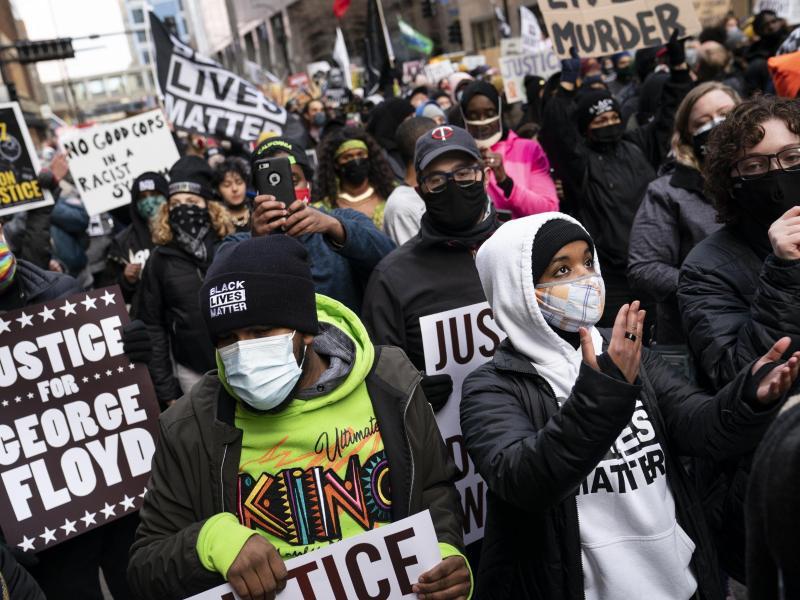 Demonstranten gehen in Minneapolis mit Plakaten auf die Straße und fordern Gerechtigkeit. Foto: John Minchillo/AP/dpa
