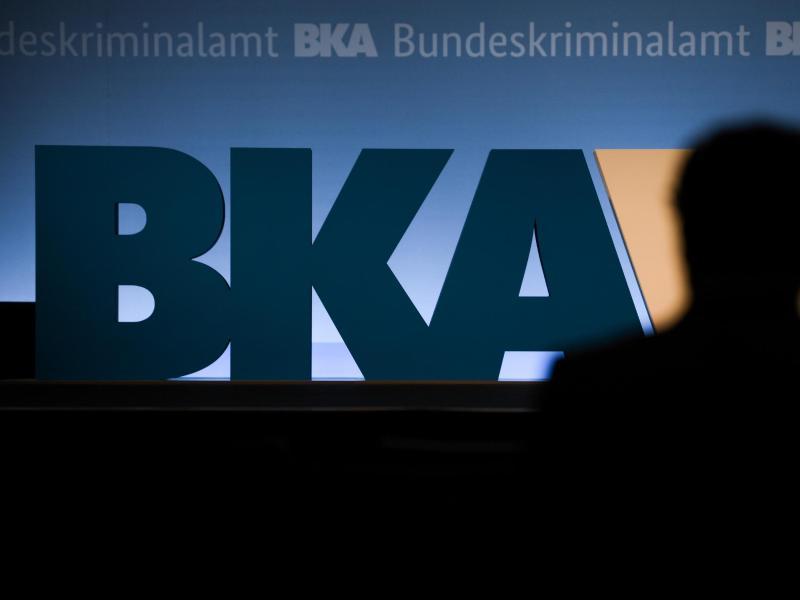 Ein Teilnehmer der BKA-Herbsttagung steht im Veranstaltungssaal des RheinMain CongressCenter (RMCC) vor dem BKA-Logo der Behörde. Foto: Arne Dedert/dpa