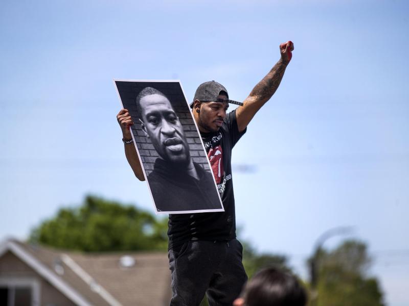 Tony L. Clark hält ein Foto des verstorbenen George Floyd. Der ehemalige Polizist Derek Chauvin ist schuld an der Tötung des unbewaffneten Afroamerikaners. Foto: Jerry Holt/Star Tribune/AP/dpa
