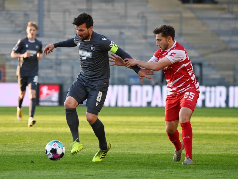 KSC-Profi Jérôme Gondorf (l) schirmt den Ball gegen den Würzburger Dominik Meisel ab. Foto: Uli Deck/dpa