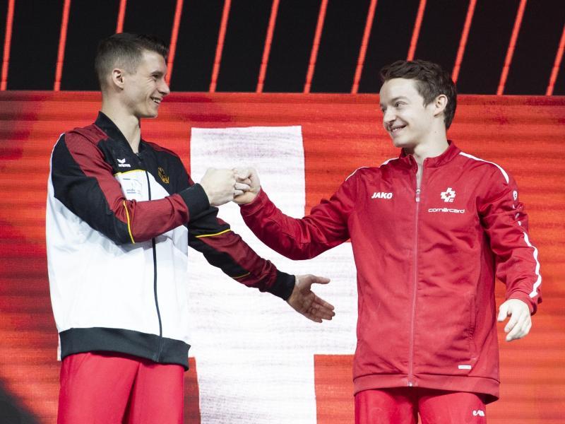 Lukas Dauser (l) und Christian Baumann aus der Schweiz freuen sich auf dem Podium über ihren gemeinsamen dritten Platz. Foto: Georgios Kefalas/KEYSTONE/dpa