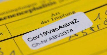 """Ein Aufkleber mit der Aufschrift """"Cov19VacAstraZ"""" in einem Impfausweis. Foto: Rolf Vennenbernd/dpa"""