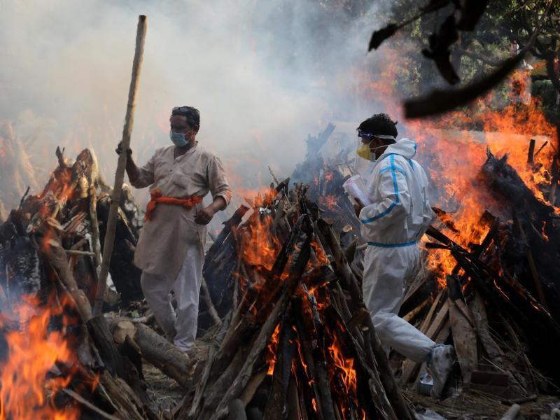 Neu-Delhi: Angehörige neben brennenden Scheiterhaufen von Opfern, die an den Folgen einer Corona-Infektion gestorben sind. Foto: Naveen Sharma/SOPA/ZUMA/dpa