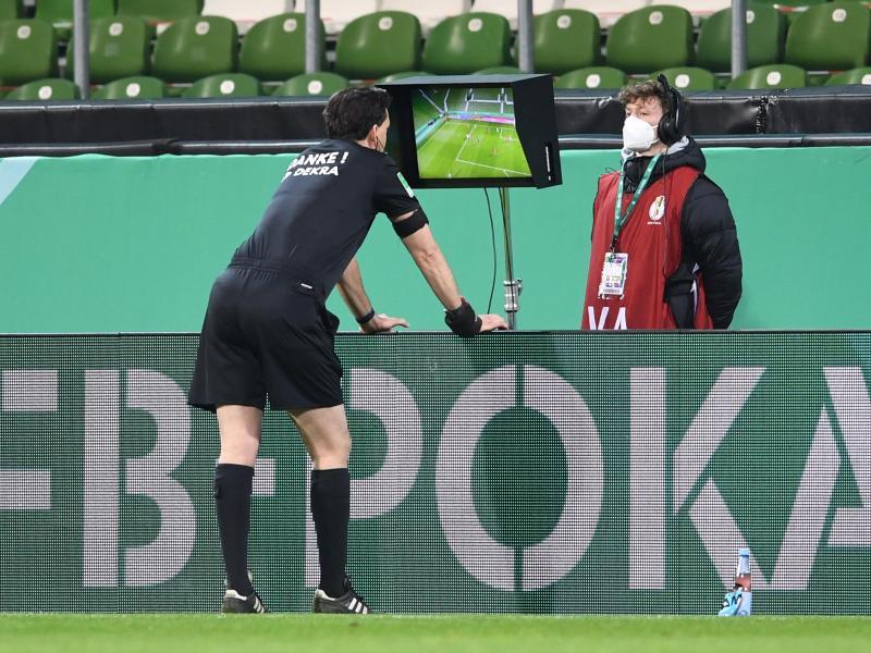 Schiedsrichter Manuel Gräfe nimmt den Videobeweis zu Hilfe und nimmt einen gegebenen Elfmeter zurück. Foto: Carmen Jaspersen/dpa