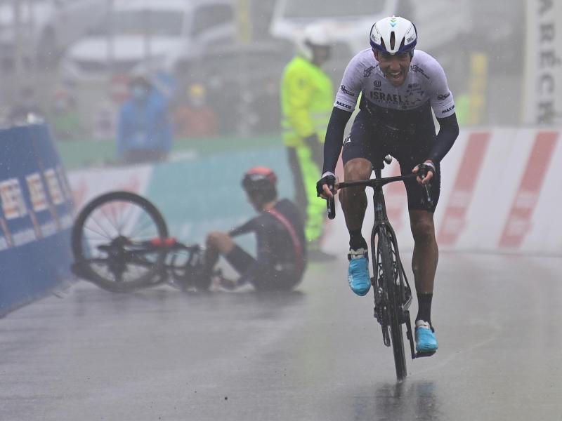 Michael Woods überquert als Etappensieger die Ziellinie. Im Hintergrund liegt der gestürzte Geraint Thomas am Boden. Foto: Jean-Christophe Bott/KEYSTONE/dpa