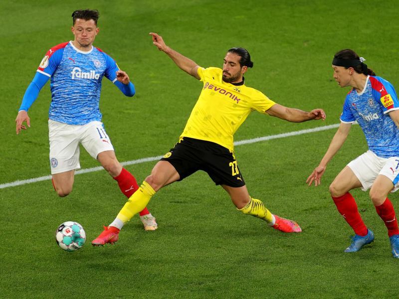 Dortmunds Emre Can (M) kommt vor Kiels Fabian Reese (l) an den Ball. Foto: Friedemann Vogel/epa Pool/dpa