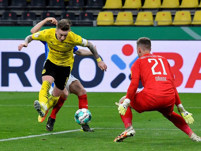 Marco Reus schießt im Fallen das Dortmunder 3:0. Foto: Martin Meissner/AP Pool/dpa