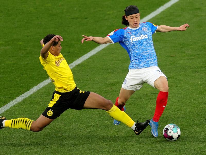 Dortmunds Jude Bellingham (l) im Zweikampf mit Kiels Jae-Sung Lee. Foto: Friedemann Vogel/epa Pool/dpa