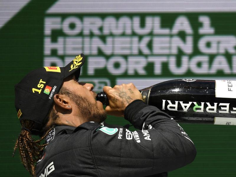 Sieger Hamilton gönnt sich auf dem Podium einen Schluck Champagner. Foto: Gabriel Bouys/Pool AFP/dpa