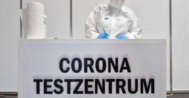 Eine Mitarbeiterin in Schutzkleidung steht im Corona-Testzentrum in der Messe Erfurt bereit. Foto: Martin Schutt/dpa-Zentralbild/dpa