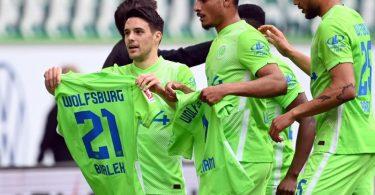 Wolfsburgs Josip Brekalo (l) bejubelt sein Tor zum 1:0 mit einem Trikot von Bartosz Bialek. Foto: Swen Pförtner/dpa