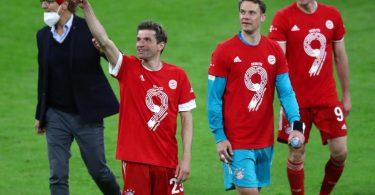 Thomas Müller (l-r), Torwart Manuel Neuer und Robert Lewandowski tragen zu ihrer 9. deutschen Meisterschaft in Folge rote T-Shirts mit einer großen Neun. Foto: Matthias Schrader/AP-Pool/dpa